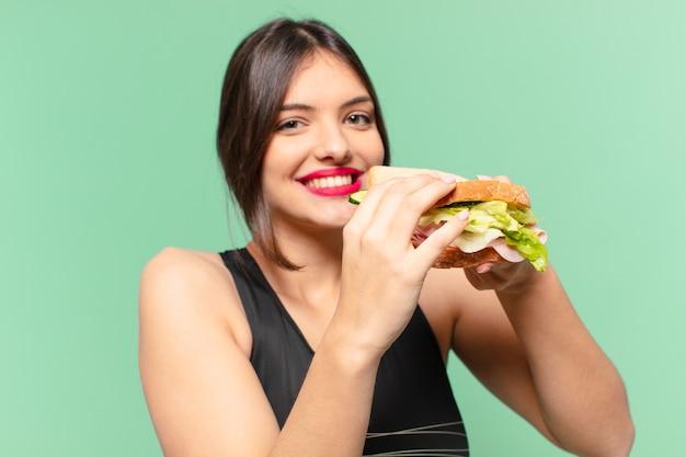 젊은 예쁜 스포츠 여자 행복 식과 샌드위치를 들고