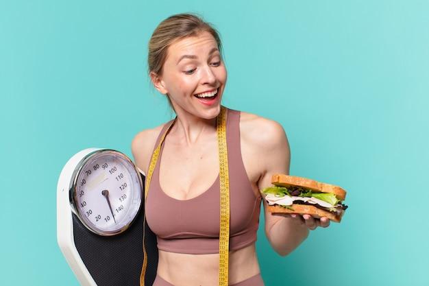 Молодая красивая спортивная женщина счастливое выражение и держит весы и бутерброд