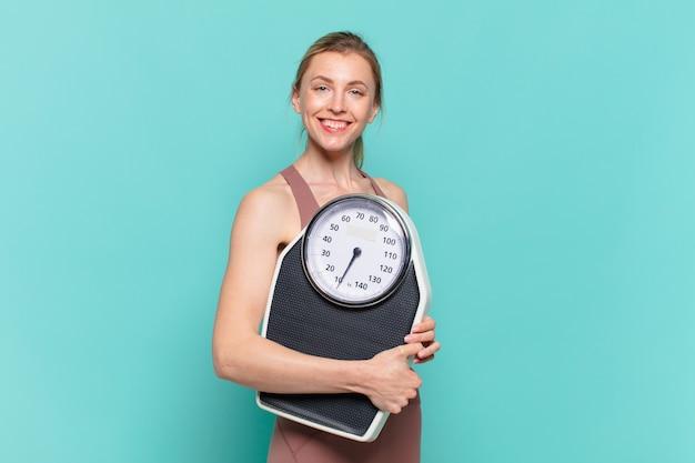 Молодая красивая спортивная женщина счастливым выражением и держит весы