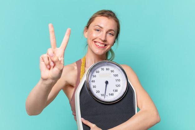 Молодая красивая спортивная женщина счастливое выражение и держит весы