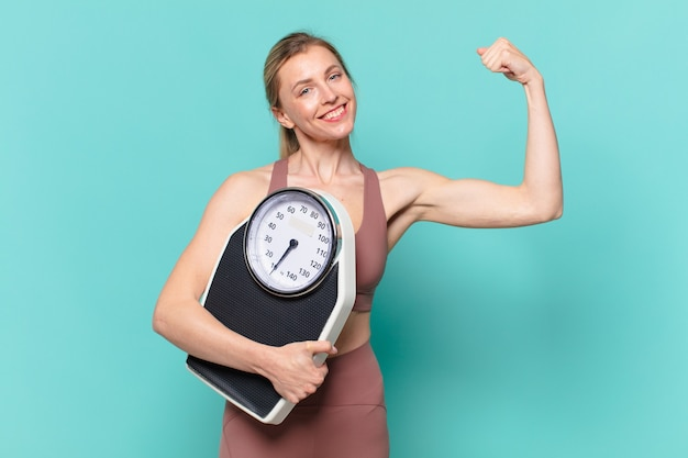 Young pretty sport woman happy expression and holding a weight scale