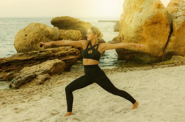 野生のビーチで砂の上でアーサナ運動を練習しているスポーツウェアの若いかわいいスポーツ女性。屋外ヨガトレーニング