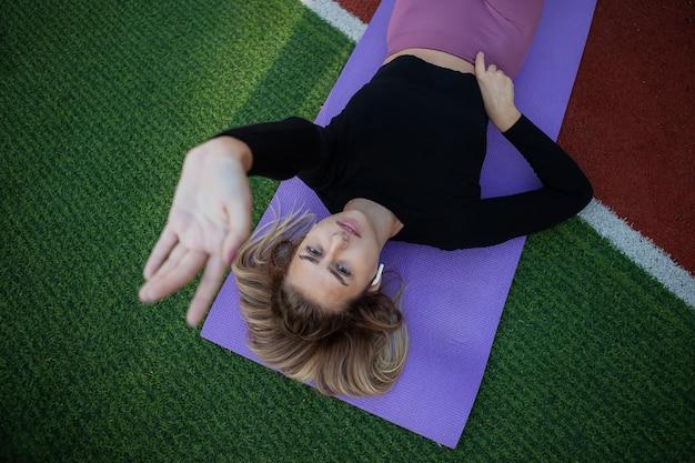 젊은 예쁜 스포츠 여자는 매트에 쉬고 있다. 패션샷. 야외 운동