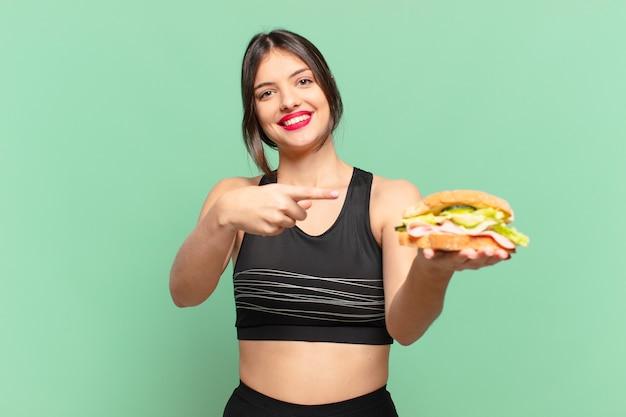 Молодая красивая спортивная женщина, указывающая или показывающая и держащая бутерброд