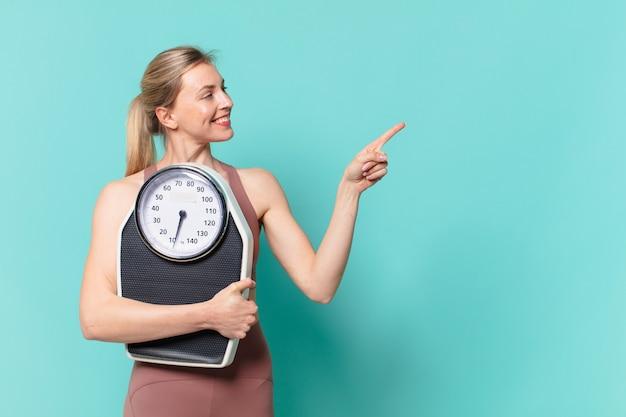 Молодая красивая спортивная женщина, указывающая или показывающая и держащая весы