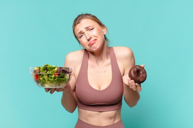Молодая красивая спортивная женщина с грустным выражением лица, держащая бутерброд и пончик