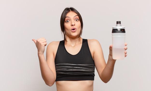 若いかわいいスポーツの女性は表情を怖がらせ、水筒の飲み物を持っています