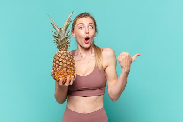 Молодая красивая спортивная женщина удивлена выражением лица и держит ананас