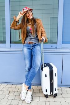 Молодая красивая спортивная девушка позирует с багажом возле аэропорта