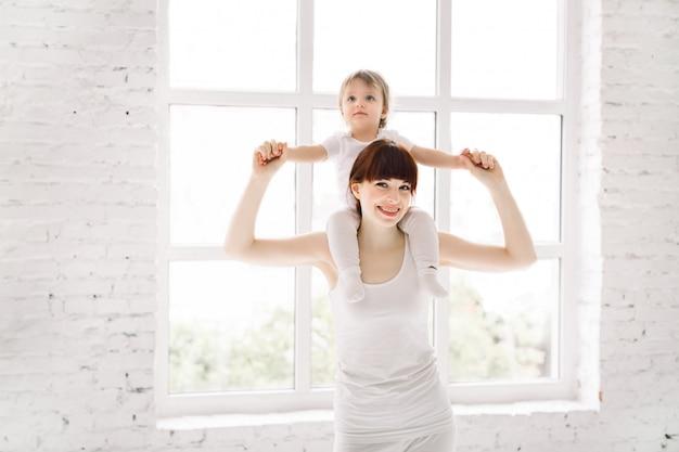 Молодая довольно спортивная мать, спекуляция ее малыша девочка в белой одежде фитнес на фоне большого окна