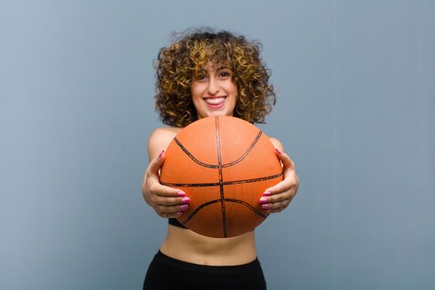 바구니 공 피트 니스 옷을 입고 젊은 예쁜 스포츠 여자 프리미엄 사진