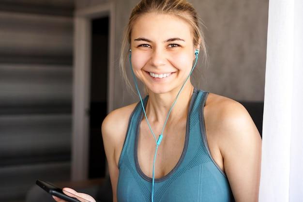 집에서 꽤 스포티 한 소녀가 스마트 폰에서 헤드폰으로 음악을 듣는다.
