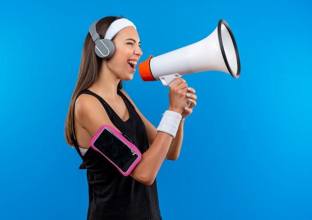 ヘッドバンドとリストバンドとヘッドフォンを身に着けている若いかなりスポーティーな女の子は、縦断ビューで立っているスピーカーによって話している電話の腕章と