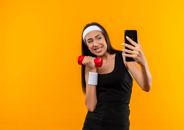 Молодая симпатичная спортивная девушка с повязкой на голову и браслетом с гантелями и селфи