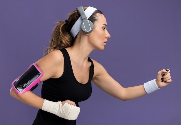 Giovane ragazza abbastanza sportiva che indossa le cuffie con i polsini della fascia e la fascia da braccio del telefono con il polso ferito avvolto con una benda
