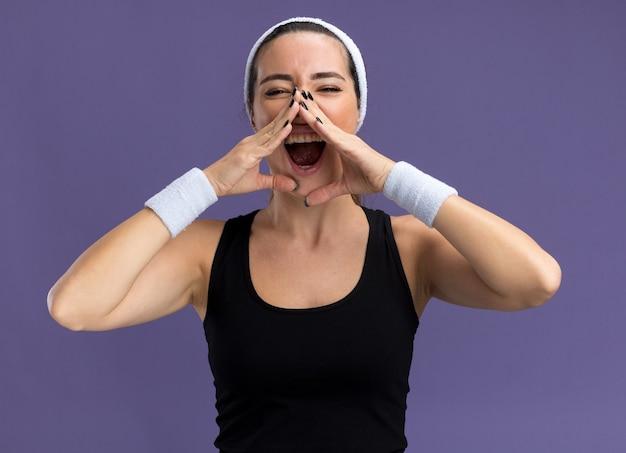 Giovane ragazza abbastanza sportiva che indossa fascia e braccialetti tenendo le mani intorno alla bocca chiamando ad alta voce qualcuno isolato su muro viola