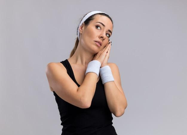 머리띠와 팔찌를 착용한 젊고 스포티한 여성이 복사 공간이 있는 흰색 벽에 격리된 상태로 수면 제스처를 취하고 있습니다.