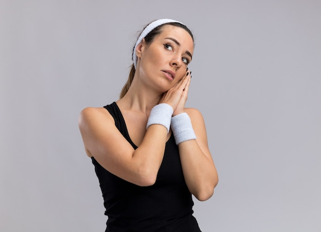 Giovane donna abbastanza sportiva che indossa fascia e braccialetti che fanno il gesto del sonno guardando in alto isolato sul muro bianco con copia spazio