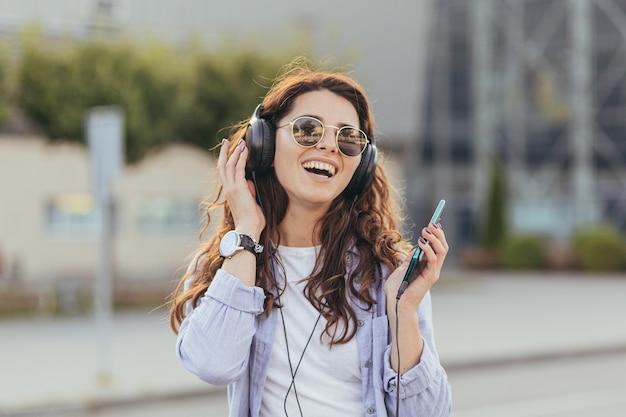 タクシーの車を待って、音楽を聴いている若いかわいい学生の女の子