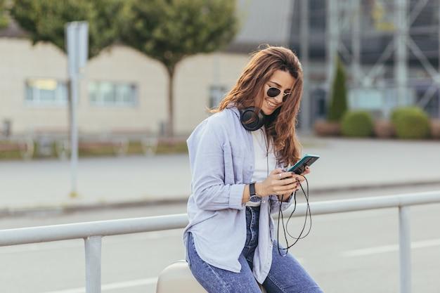 Молодая красивая девушка студент ждет машину такси и слушает музыку