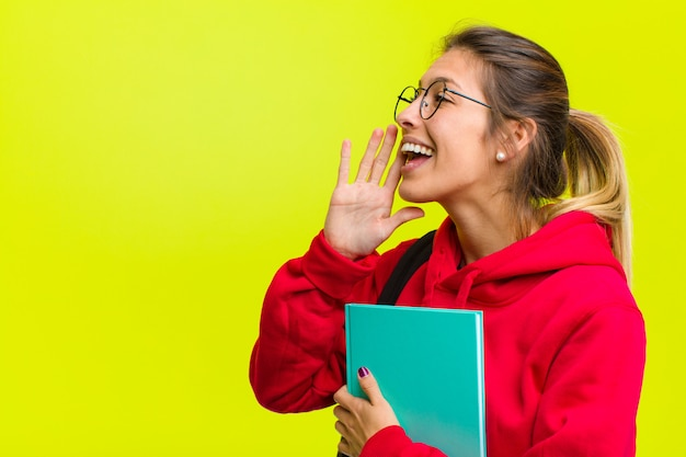Young pretty student profile view looking happy and excited shouting and calling to copy space on the side