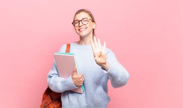 Молодой симпатичный студент улыбается и выглядит дружелюбно, показывает номер четыре или четвертый с рукой вперед, отсчитывая