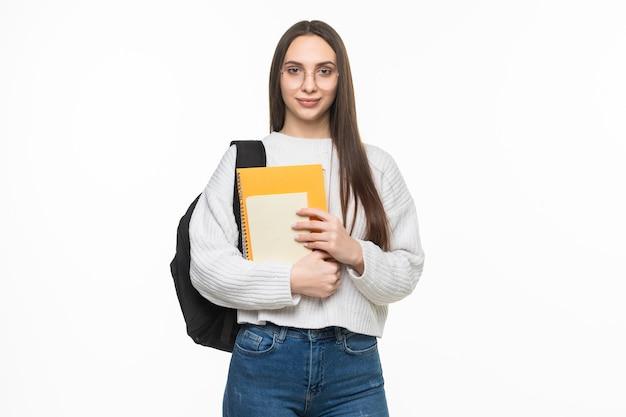 배낭과 운동 책을 가진 젊은 예쁜 학생 여자. 흰 벽에 고립