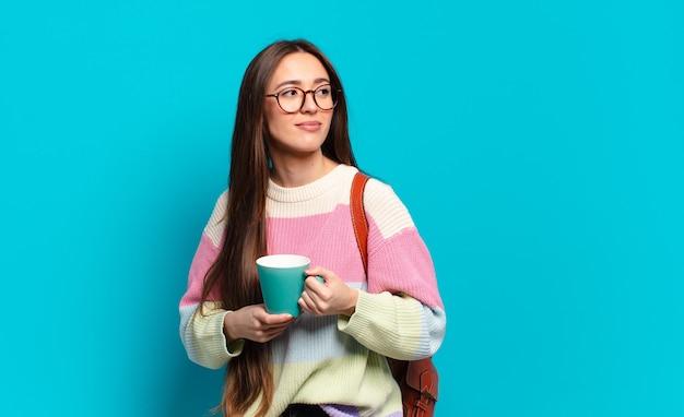 Молодая женщина довольно студент женщина с чашкой кофе