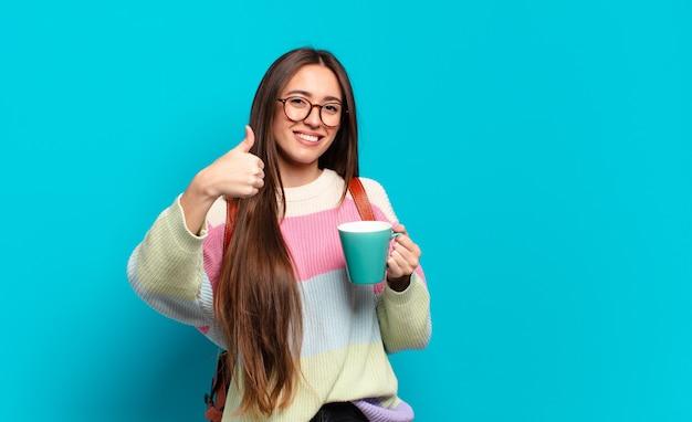 コーヒーカップを持つ若いきれいな学生女性女性