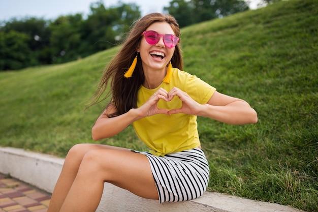 Молодая довольно стильная счастливая улыбающаяся женщина веселится в городском парке, позитивная, эмоциональная, в желтом топе, полосатой мини-юбке, розовых солнцезащитных очках, модная тенденция в летнем стиле, показывает знак сердца