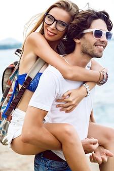 Giovane coppia di hipster abbastanza elegante innamorata divertendosi e abbracci alla fantastica spiaggia di pietra nella piovosa giornata estiva