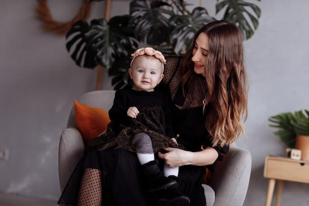 ハグと自宅の椅子に座って幸せな笑顔の家族、ライフスタイルの人々のコンセプトの暗いドレスの小さなかわいい娘と若いかなりスタイリッシュな母親。母の日、赤ちゃんの日