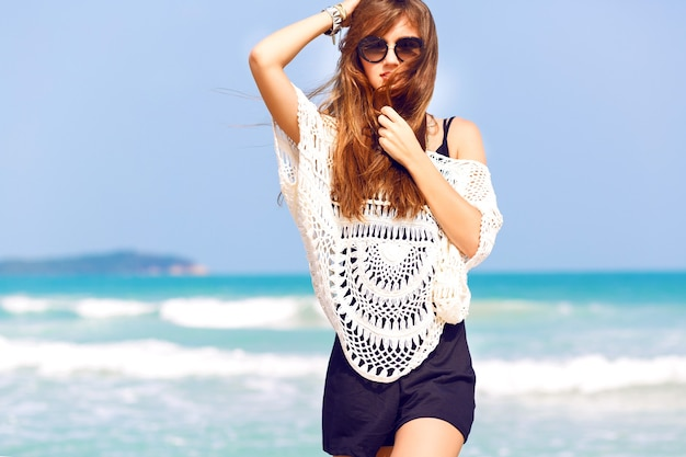 青い海と素晴らしい熱帯のビーチでポーズをとる若いかなりスタイリッシュな官能的な女性は、彼女の休暇と風の強い夏の晴れた日をお楽しみください。プレイスーツとサングラスを着用
