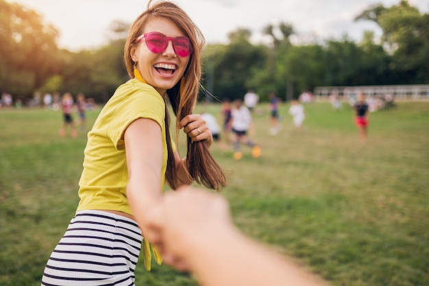 Young pretty stylish smiling woman having fun in city park, holding hand of boyfriend, follow me, positive emotional, wearing yellow top, pink sunglasses, summer style fashion trend