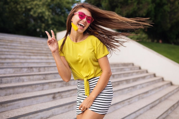Young pretty stylish smiling woman having fun in city park, positive, emotional, wearing yellow top, striped mini skirt, pink sunglasses, summer style fashion trend, long hair, showing peace sign