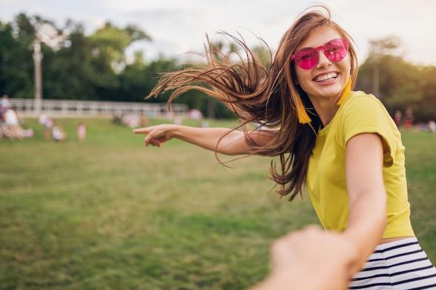 都市公園で楽しんでいる、ボーイフレンドの手を握って、私に従ってください、前向きで、感情的で、黄色いトップを着て、ピンクのサングラス、夏のスタイルのファッショントレンド、前向きな感情