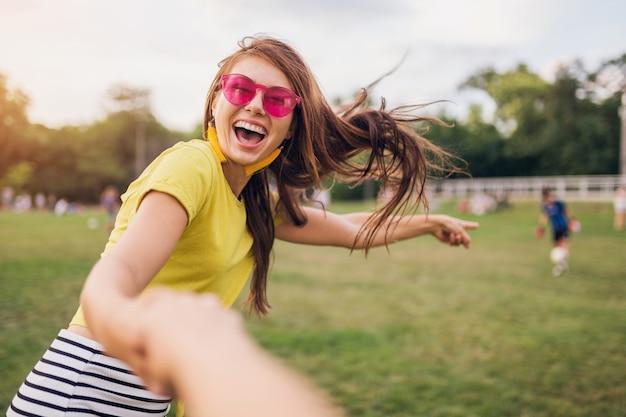 都市公園で楽しんでいる、ボーイフレンドの手を握って、私に従ってください、ポジティブな感情的な、黄色いトップ、ピンクのサングラス、夏のスタイルのファッショントレンドを楽しんでいる若いかなりスタイリッシュな笑顔の女性