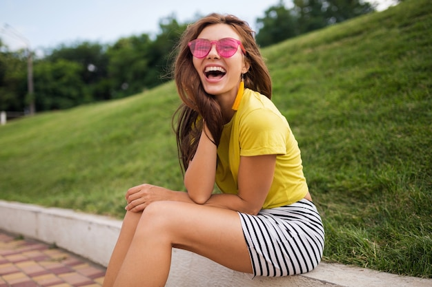 Молодая довольно стильная улыбающаяся женщина веселится в городском парке, позитивная, эмоциональная, в желтом топе, полосатой мини-юбке, розовых солнцезащитных очках, модная тенденция в летнем стиле, счастливое настроение