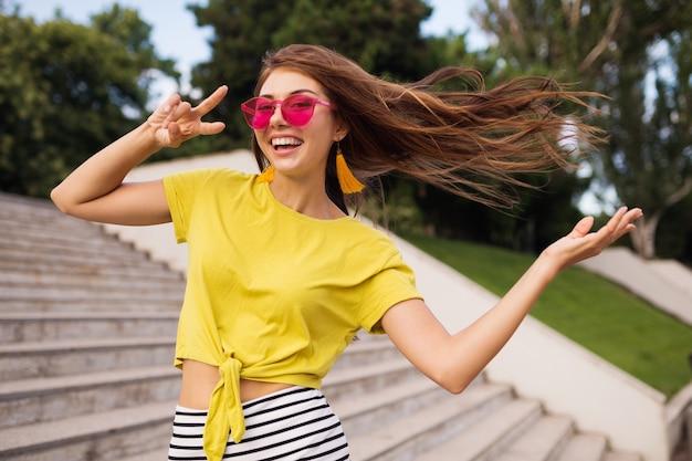 Молодая довольно стильная улыбающаяся женщина веселится в городском парке, позитивная, эмоциональная, в желтом топе, полосатой мини-юбке, розовых солнцезащитных очках, модная тенденция в летнем стиле, длинные волосы, показывая знак мира