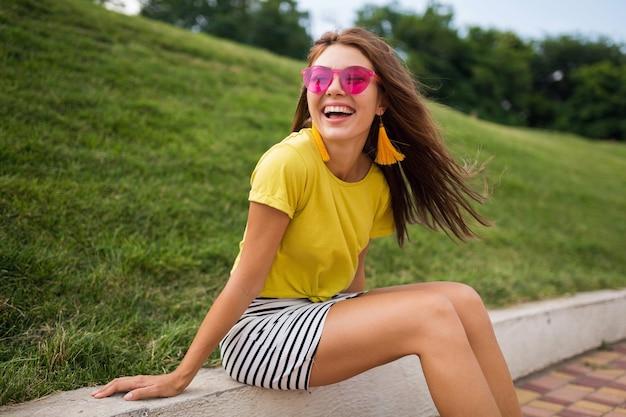 Молодая довольно стильная улыбающаяся женщина веселится в городском парке, позитивная, эмоциональная, в желтом топе, полосатой мини-юбке, розовых солнцезащитных очках, модная тенденция в летнем стиле, позитивные эмоции
