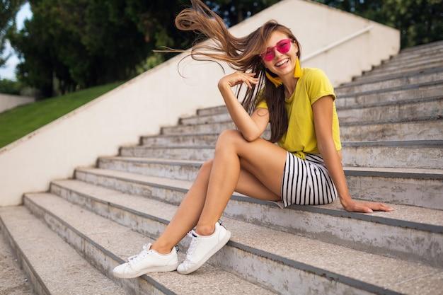 黄色のトップ、縞模様のミニスカート、ピンクのサングラス、白いスニーカー、夏のスタイルのファッショントレンド、長い脚、階段に座って、長い髪を着て、都市公園で楽しんでいる若いかなりスタイリッシュな笑顔の女性