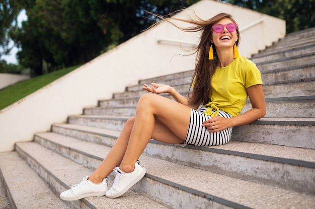 Молодая довольно стильная улыбающаяся женщина веселится в городском парке, одетая в желтый топ, полосатую мини-юбку, розовые солнцезащитные очки, белые кроссовки, модную тенденцию в летнем стиле, длинные ноги, сидя на лестнице, длинные волосы