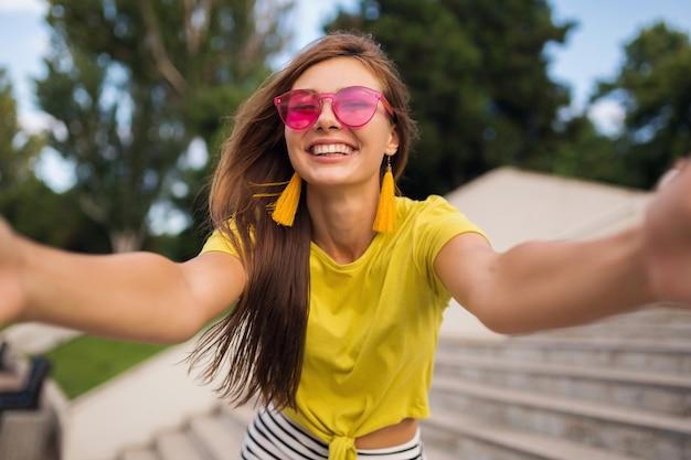 Giovane donna sorridente piuttosto elegante che fa selfie nel parco cittadino, positivo, emotivo, con indosso top giallo, occhiali da sole rosa, tendenza moda stile estivo, capelli lunghi, divertirsi
