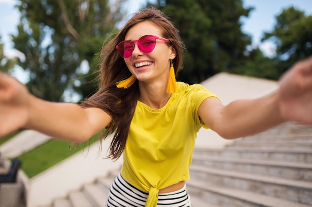 Young pretty stylish smiling woman making selfie in city park, positive, emotional, wearing yellow top, pink sunglasses, summer style fashion trend, long hair, having fun