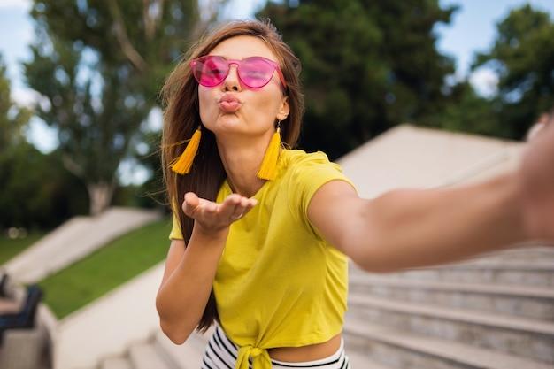 都市公園で自分撮りを作る若いかなりスタイリッシュな笑顔の女性、ポジティブ、感情的、黄色のトップ、ピンクのサングラス、夏のスタイルのファッショントレンド、長い髪、楽しんで