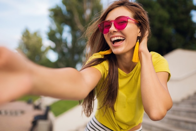 Молодая довольно стильная улыбающаяся женщина, делающая селфи в городском парке, позитивная, эмоциональная, в желтом топе, розовых очках, модная тенденция в летнем стиле, длинные волосы, весело