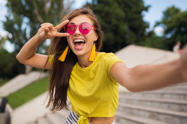 都市公園で自分撮りを作る若いかなりスタイリッシュな笑顔の女性、ポジティブ、感情的、黄色のトップ、ピンクのサングラス、夏のスタイルのファッショントレンド、長い髪、ピースサインを表示