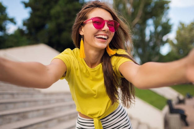 Young pretty stylish smiling woman making selfie photo in city park, positive, emotional, wearing yellow top, pink sunglasses, summer style fashion trend, long hair, having fun