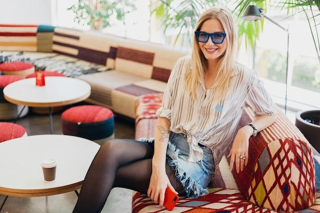 Giovane donna sorridente abbastanza elegante che si siede nel caffè hipster sul divano che indossa camicia e occhiali da sole blu