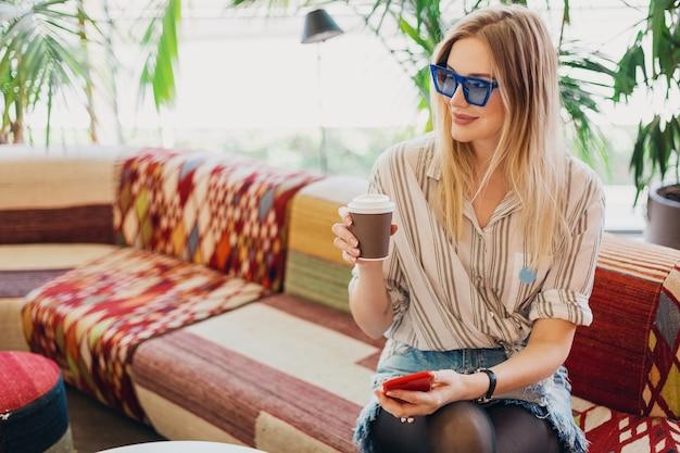 Молодая довольно стильная улыбающаяся женщина, сидящая в хипстерском кафе на диване в рубашке и синих солнцезащитных очках, пьет кофе